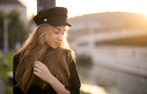 Woman wearing black hat smiling with closed eyes Stock Photo