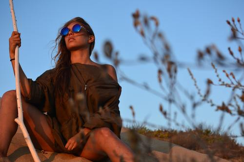 Woman wearing sunglasses holding wooden stick sitting on the desert Stock Photo