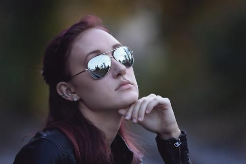 Woman with hand on chin wearing sunglasses and nose ring Stock Photo