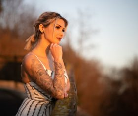 Woman with tattoo on arm looks into the distance Stock Photo